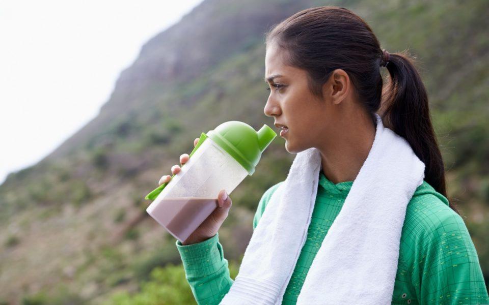 mujer joven tomando un batido de proteína